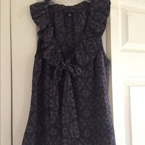 Flowing, patterned navy top with ruffle & bow.