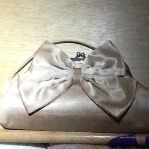 A pretty golden clutch with bow detail.
