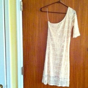 Cream colored one shoulder lace dress.
