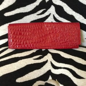 Red clutch with alligator detail.