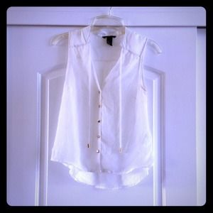 Sheer sleeveless white blouse with gold accents.