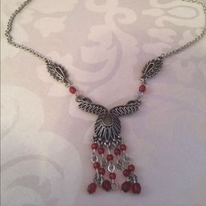 Silver tone metal necklace with red beads