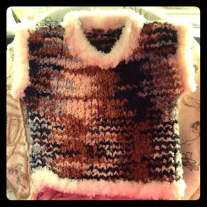 Hand knitted baby vest.