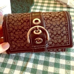 Black coach wallet with buckle front.