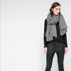 Houndstooth knit scarf with frayed edges.