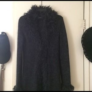 Long sweater coat with fur like trim all around.