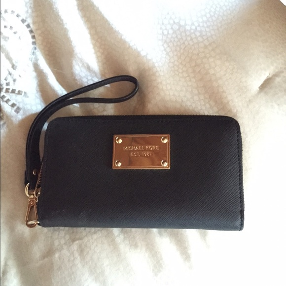 41faf6a5caea Black and gold Michael Kors wristlet wallet. M_551873f86d64bc4dc400d8ab