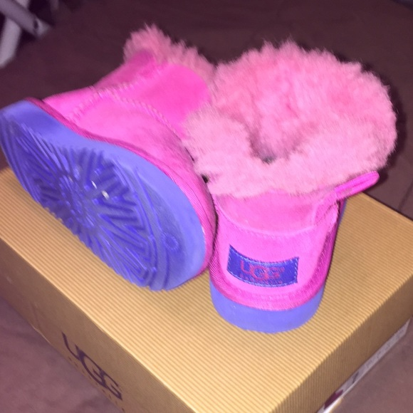 Kids' pink Uggs with royal blue sole.