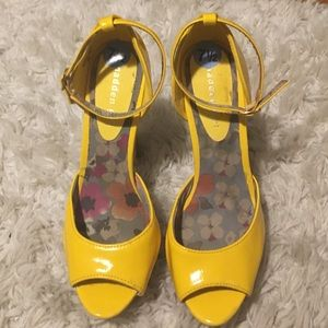 Yellow ankle strap peep toe heels.