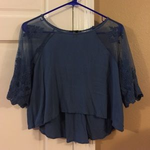Blue crop top with sheer lace sleeves.