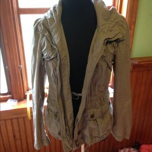 An olive green zip up jacket made w/ light fabric.