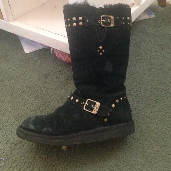 Black tall Ugg boots with gold accent buckles.