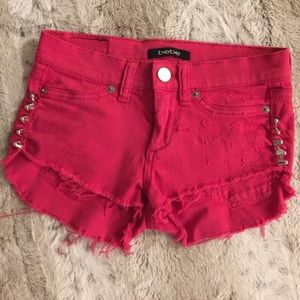 bebe Pants - Distressed  red spiked Bebe shorts