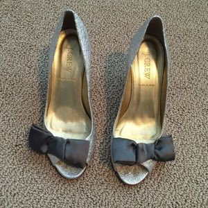 Metallic silver leather peep toes with silk bow.