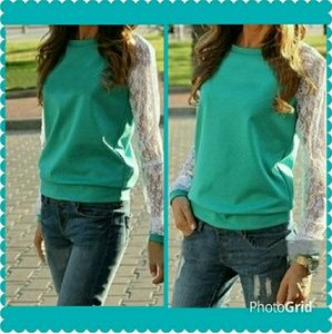 Turquoise top with white lace sleeves.