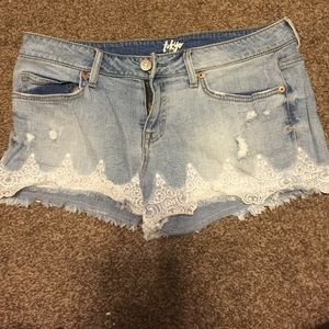 Light blue denim shorts with white lace trimming.