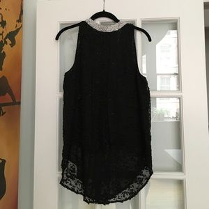 Sleeveless, flowy, black top from Anthropologie.