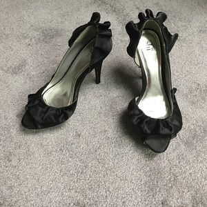 Black high heel with ruffles. Size 8.