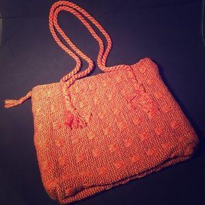 Orange woven textile zippered shoulder bag.