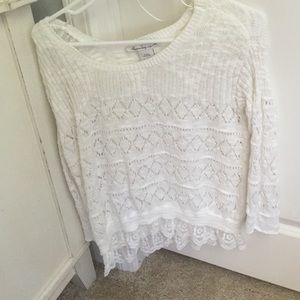 White sweater with a lace trim on the bottom
