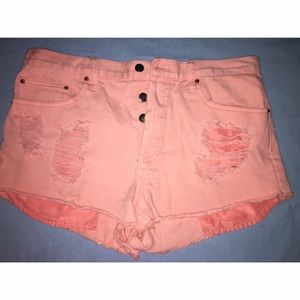 high waisted distressed coral shorts .
