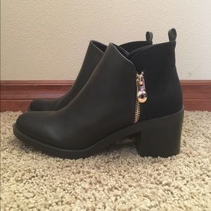 Black ankle boots with gold accent zipper