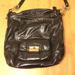 Black patent leather coach purse.