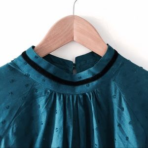 Teal-blue blouse with sleigh bells.