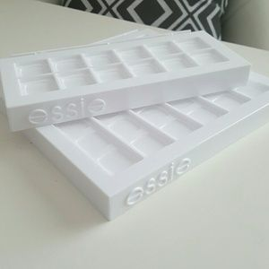 All white Essie Nail Polish stands.