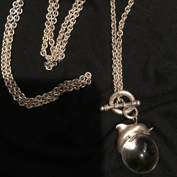 Silver necklace with dolphin on glass globe.