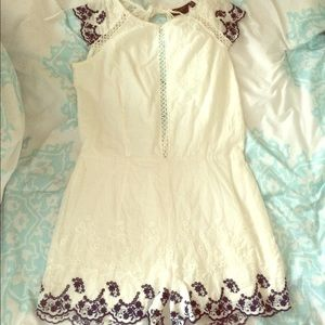 White romper with blue floral embroidery.