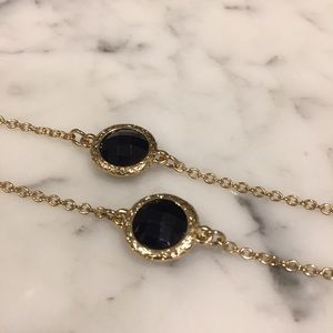 Long gold necklace with black gems