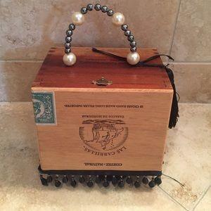 Cigar box purse with beaded handle.