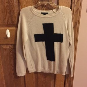 Tan sweater with black cross on the front