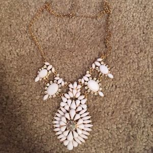 White necklace with gold chain