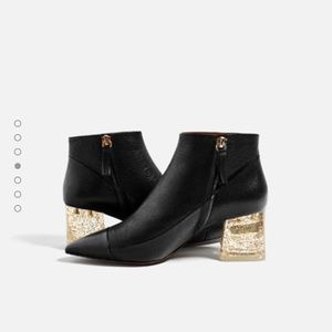 Black ankle booties with gold methacrylic heel