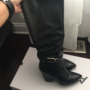 Black knee high boots with a block heel.