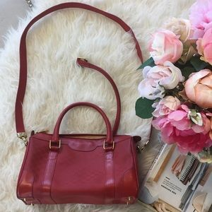Red Gucci purse with crossbody strap and handles