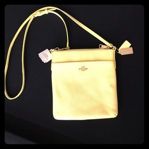 Coach pale yellow emb txt leather swing pack.