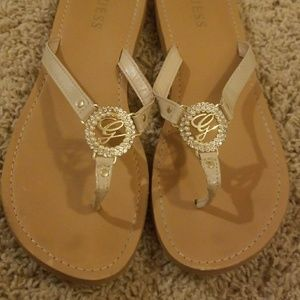 Guess: Tan flip flops with rhinestone accent