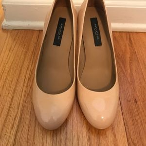 Nude patent leather pumps.