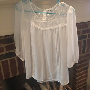 A sheer white top with lace detail at the top