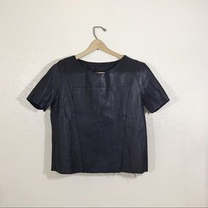 Faux leather crop top with raw hem.