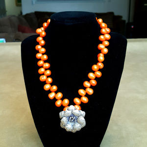 Sterling silver pendant with orange beads.