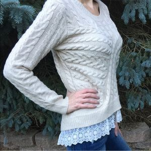 Cable knit sweater with lace trim bottom.
