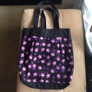Black tote bag with skull/crossbones, pink/purple