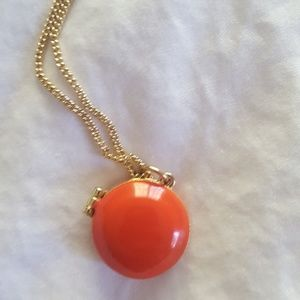 Gold necklace with orange circle locket.