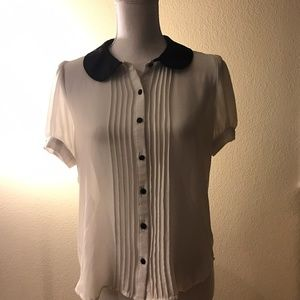 White blouse with black collar and buttons