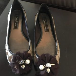 Brown coach shows with a flower charms