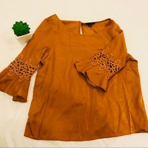 Burnt orange bell sleeve blouse with lace detail
